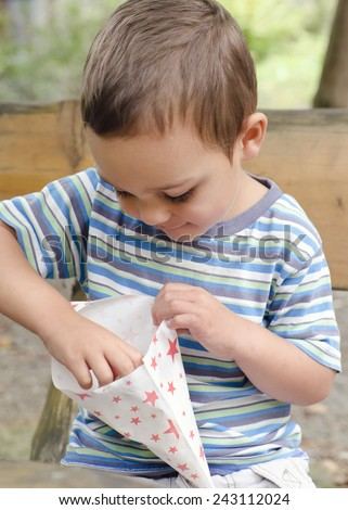 Child eating popcorn from a paper bag, while sitting on a bench in a park or garden.  - stock photo