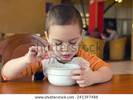Child eating soup from a bowl in a restaurant  - stock photo