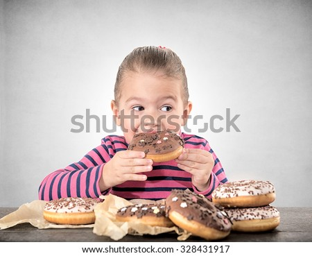 Child eating sweet chocolate donuts,selective focus