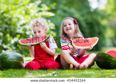 Child eating watermelon in the garden. Kids eat fruit outdoors. Healthy snack for children. Little girl and boy playing in the garden biting a slice of water melon.  - stock photo