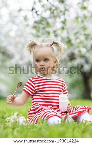 Child eating yogurt in a spring floral park - stock photo