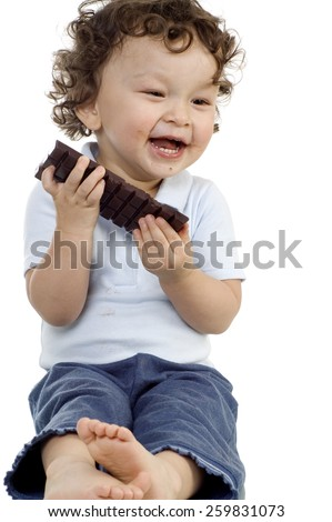 Child eats chocolate, isolated on a white background.