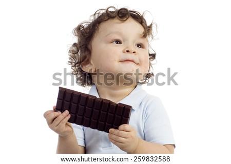 Child eats chocolate; isolated on a white background. - stock photo
