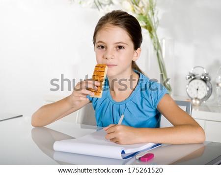 child eats snack while studying - stock photo