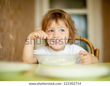 child eats with spoon in home - stock photo