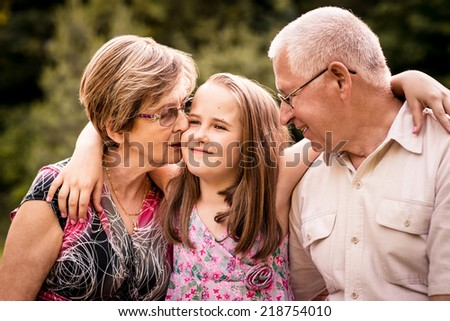 Child embracing her happy grandparents - outdoors in nature - stock photo