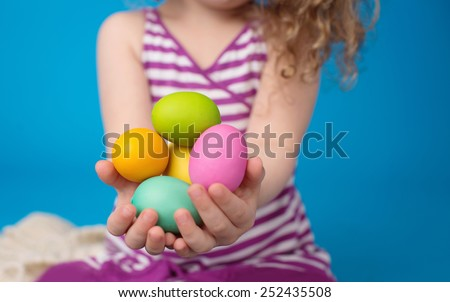 Child engaged in an Easter Activity with a Bunny and Eggs in a Basket - stock photo