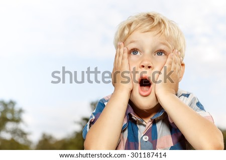 Child expressing surprise with hands on his face - stock photo