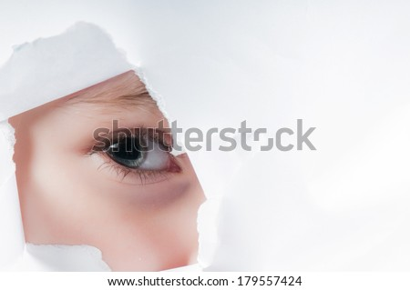 Child eye looking through a hole in paper