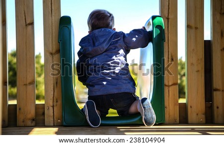 Child facing the big world! Infant playing on slide, with themes of facing your fears, challenges, health, playing, confidence and child development. - stock photo