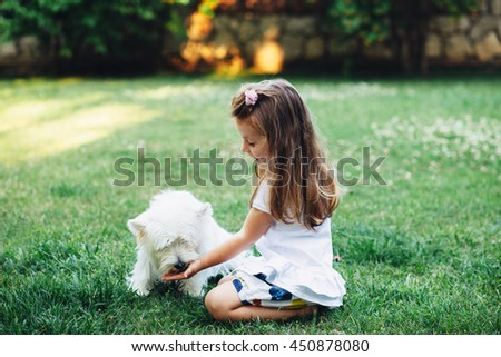 Child feeding English Highland White Terrier dog on grass in the backyard - stock photo