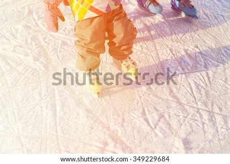 child feet learning to skate on ice in winter snow - stock photo