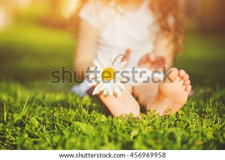 Child feet with daisy flower on green grass in a summer park. - stock photo