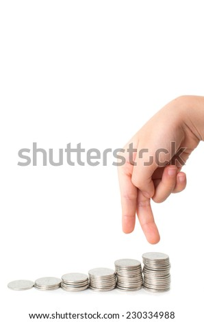 Child fingers walking down on stacks of silver coins on white background - stock photo
