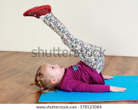 Child fitness. Little girl is doing leg lifting workout on a mat - stock photo
