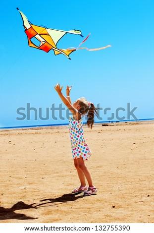 Child flying kite beach outdoor. - stock photo