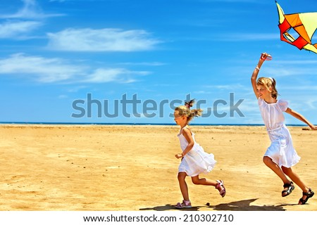 Child flying kite beach outdoor. - stock photo