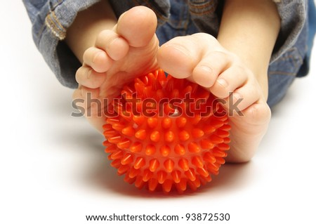 Child foots with spiny plastic orange massage ball on white background - stock photo