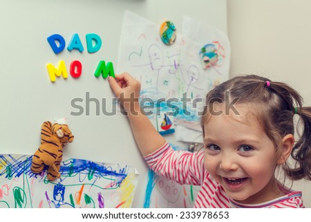 child forming mom and dad words with magnetic letters on refrigerator door.