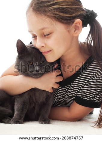 child gently hugs a gray cat
