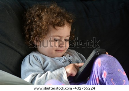 Child (girl age 2) play on mobile phone lies on a couch at home. - stock photo