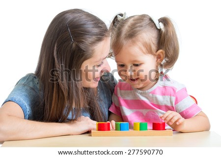 child girl and mom playing together with puzzle toy - stock photo