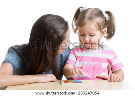 child girl and mother play together with puzzle toy - stock photo