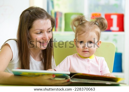 child girl and mother read a book indoors