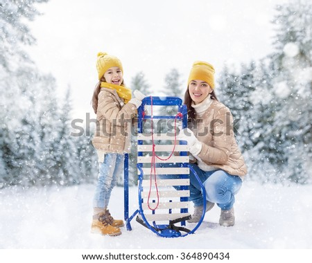Child girl and mother sledding. Family plays outdoors in snow. Outdoor fun for family winter vacation. - stock photo