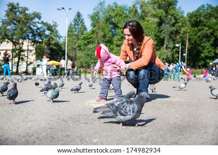 Child girl and mum playing with doves in city street. Use it for baby, parenting or love concept - stock photo