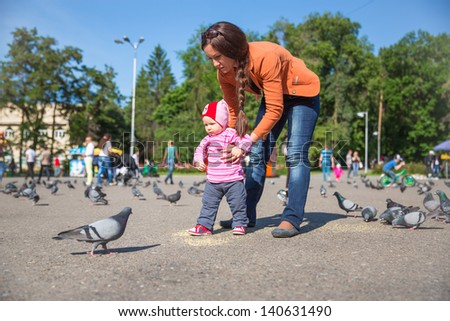 Child girl and mum playing with doves in the city street - stock photo
