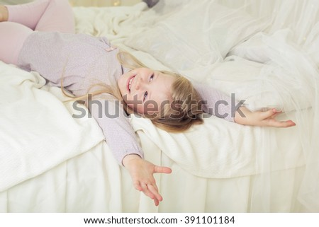 Child girl at early morning lying in bed