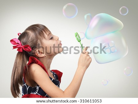 Child girl blowing soap bubble forming house, creative habitation concept