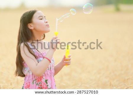 child girl blowing soap bubbles at sunset - stock photo