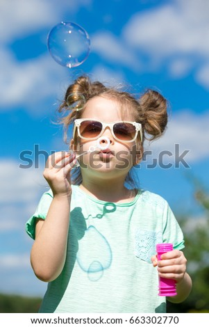 child girl blowing soap bubbles outdoor