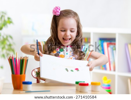 child girl drawing and showing her painting in nursery - stock photo