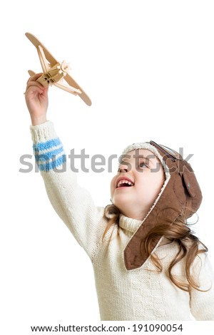 child girl dressed pilot helmet and playing with wooden airplane toy - stock photo