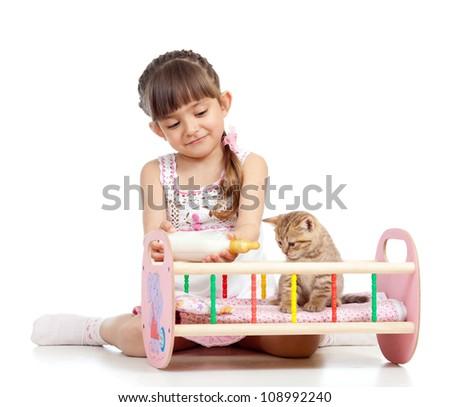 child girl feeding and playing kitten cat - stock photo