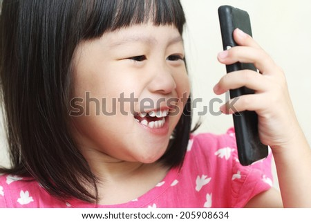 Child girl happily talking on mobile phone - stock photo