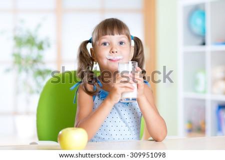 child girl having breakfast: drinking a glass of milk - stock photo