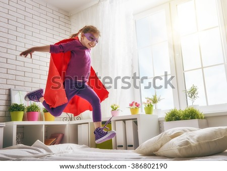 Child girl in an Superman's costume plays. The child having fun and jumping on the bed. - stock photo