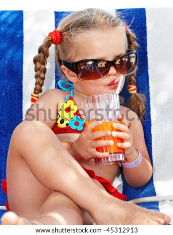 Child girl in glasses and red bikini drink juice. - stock photo