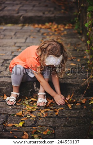 child girl in orange cardigan sitting on stone road with stairs and gathering leaves