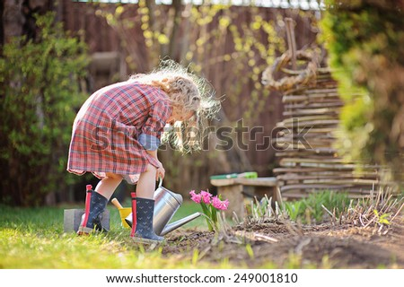 child girl in plaid dress watering flowers in spring garden - stock photo