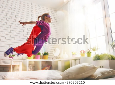 Child girl in Superhero's costume plays. The child having fun and jumping on the bed. - stock photo