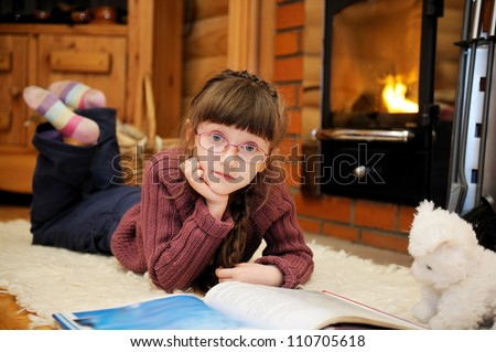 Child girl is reading a book in front of fireplace - stock photo