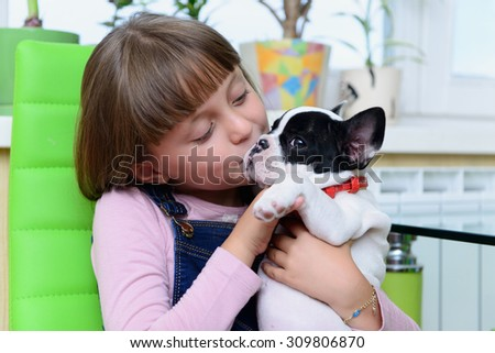 child girl kisses small pet a French Bulldog puppy  - stock photo