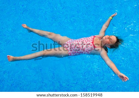 Child girl laying on the swimming pool water surface - stock photo