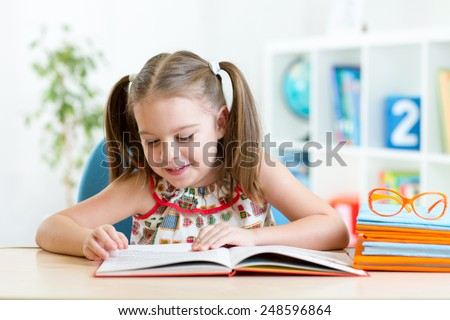 Child girl learns to read sitting at table in nursery - stock photo