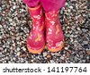 Child girl legs in pink galoshes on stone beach background - stock photo